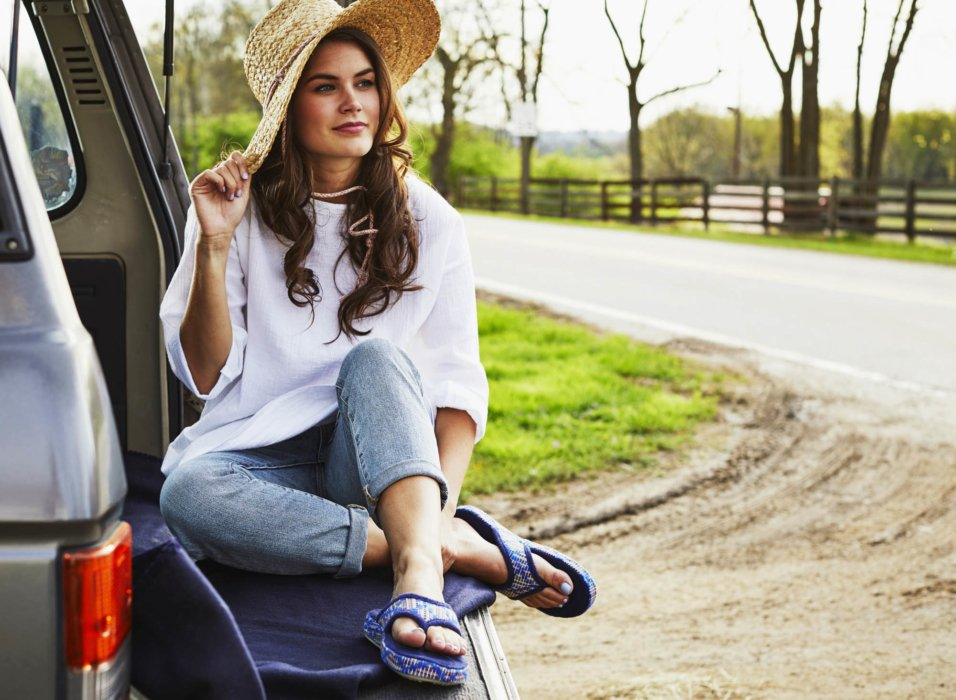 A woman sitting on the back of suv with sun hat - apparel lifestyle photography