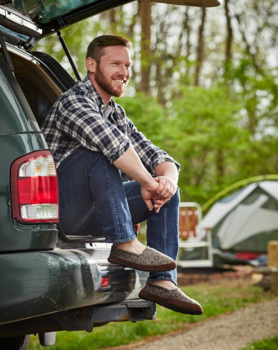 A man sitting in the back of an SUV - lifestyle photograph wearing Acorn Shoes