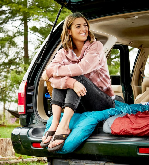 A woman sitting in the back o f an SUV with camp gear - lifestyle photography Acorn shoes