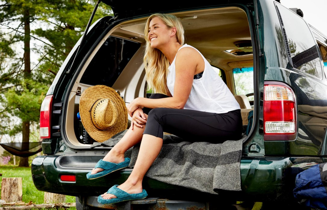 A woman sitting in the back of an SUV wearing plush sandals - Lifestyle photography Acorn Shoes