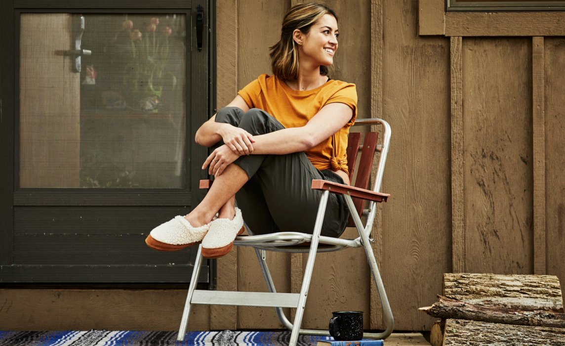 A woman sitting in a Chair outside wearing Acorn Shoes