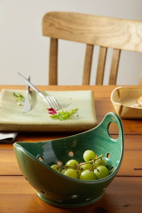 A selection of hand made craft stoneware with green grapes