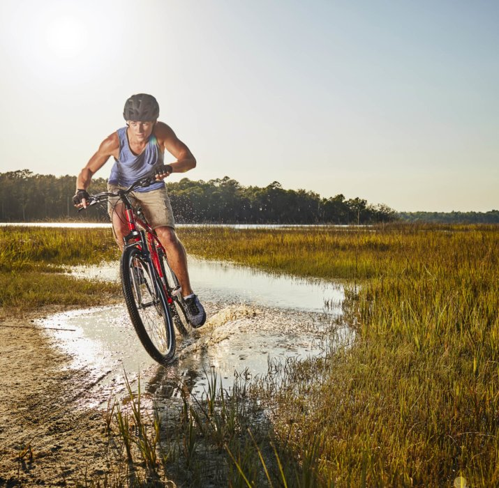 A young man riding his off road bike through a swampy terrain