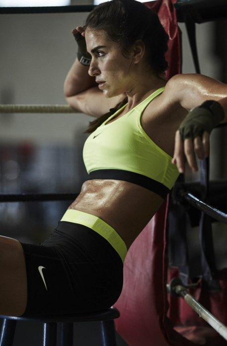 A female athlete looking sweaty after working out in boxing ring