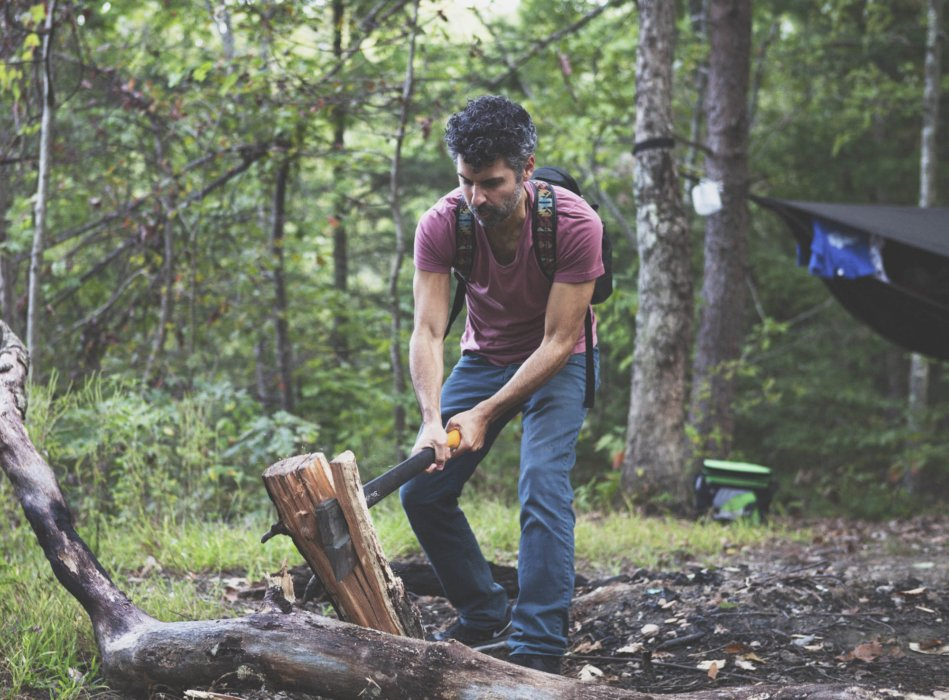 A young man splitting wood with a fiskars splitting axe outdoors