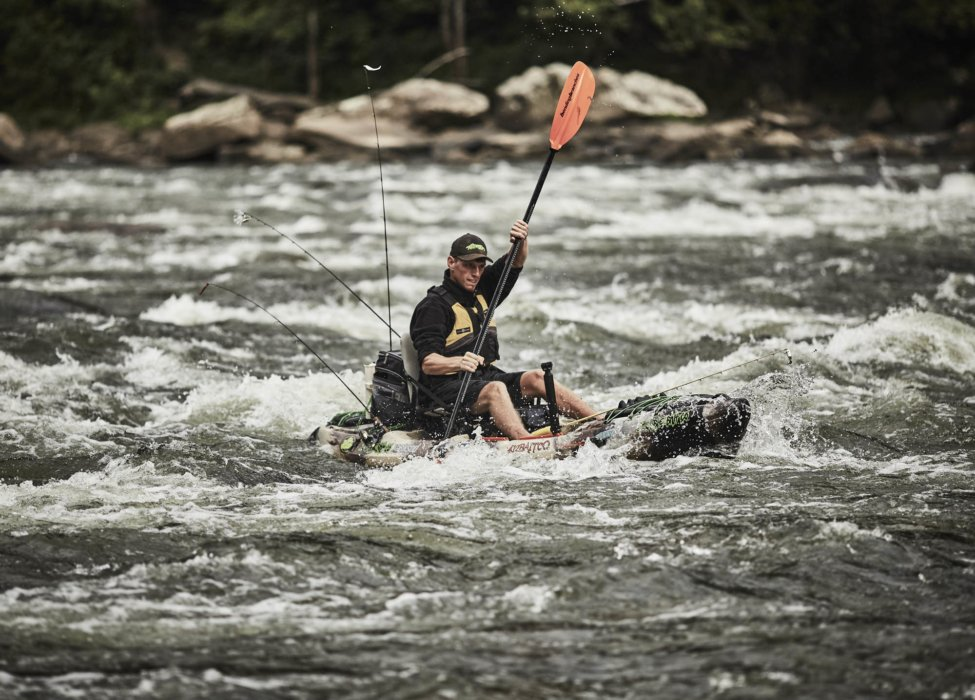 A man rowing a kayak down a treacherous river