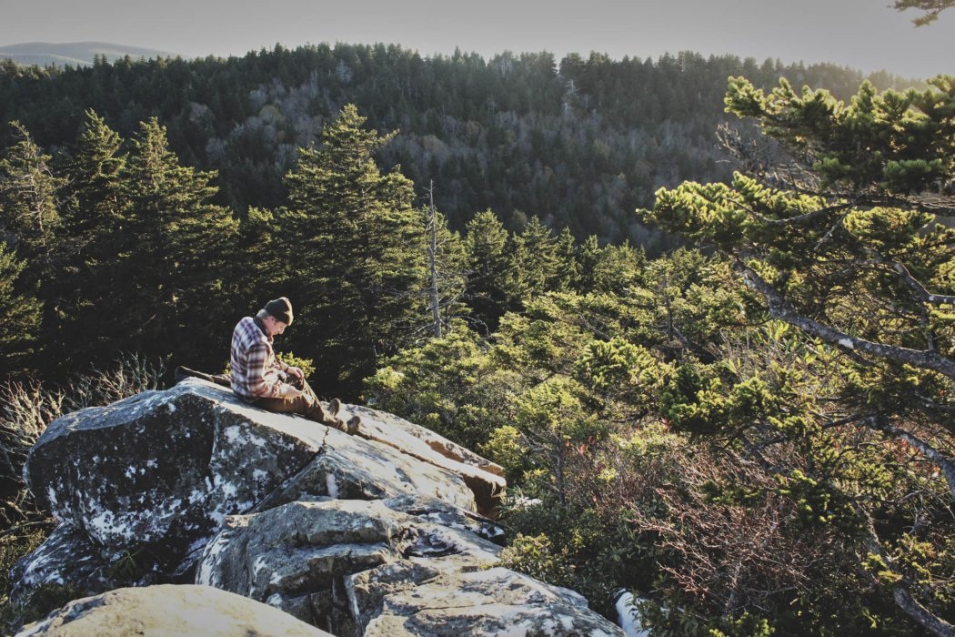 A man taking a break on a rock in the middle of hilly pine forest region