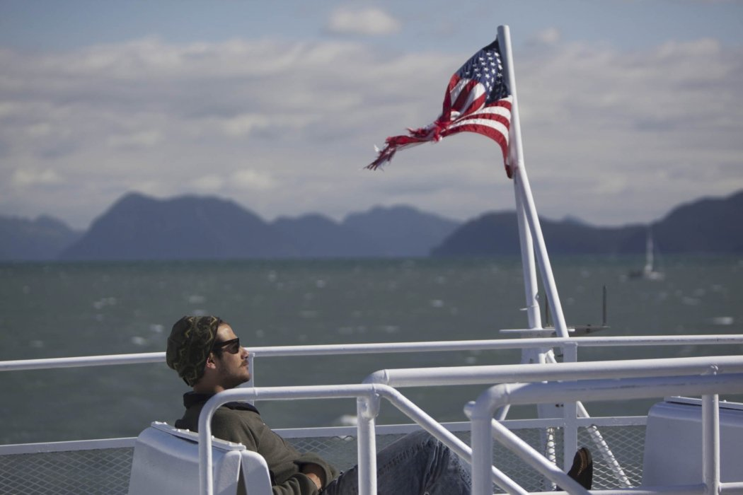 A hipster on a ferry with the American flag blowing in the wind