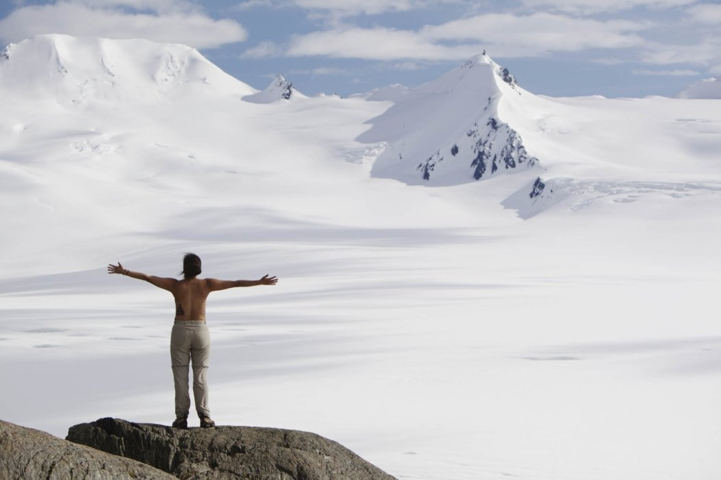 A woman with arms spread and shirtless on the top of a snow covered mountain range