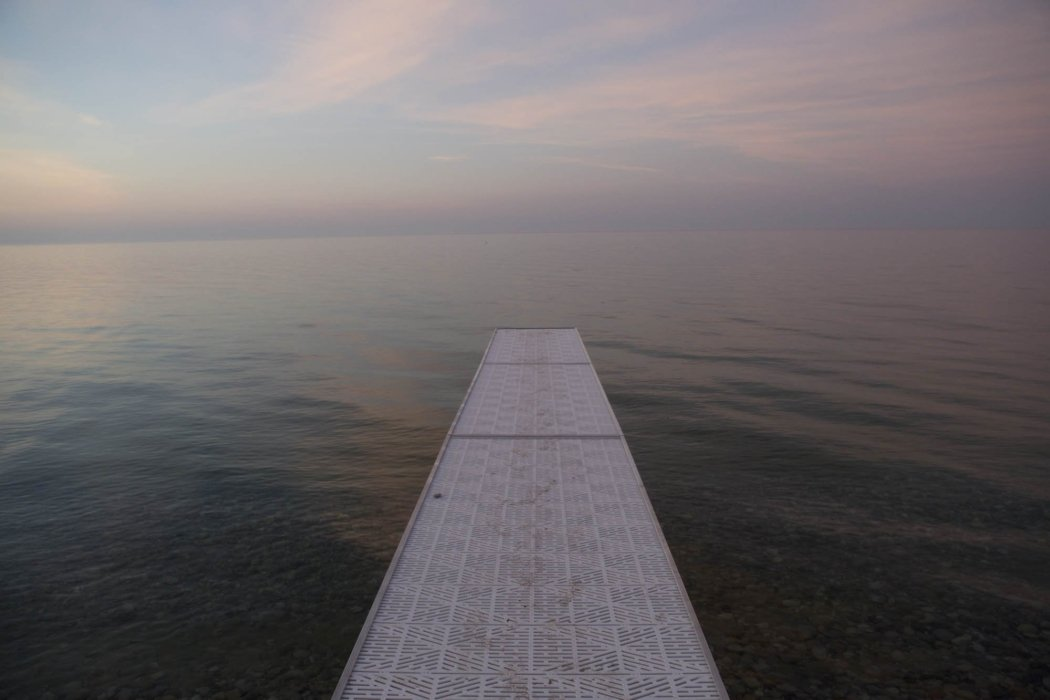 A dock on a great lake going into the pebble covered shore
