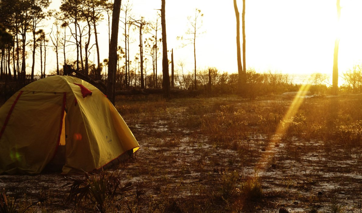 A campsite with a yellow tent during sunset on a shore