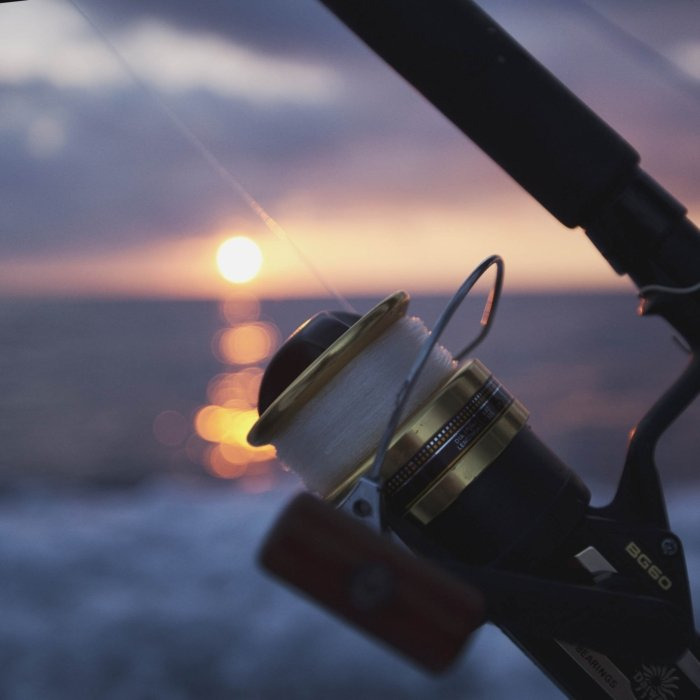 A fishing reel on a rod overlooking a sunset on the ocean