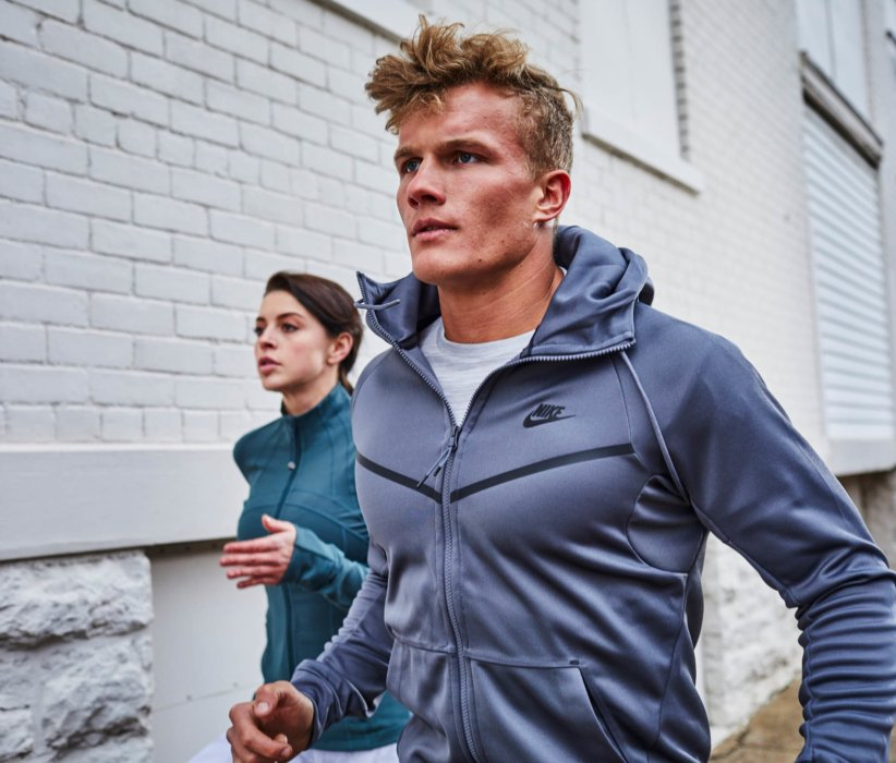 A young man and woman running in an urban setting down a sidewalk