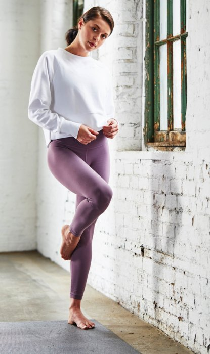A woman preparing for yoga wearing yoga apparel in an urban warehouse