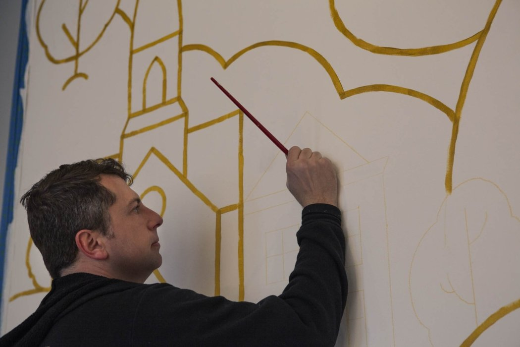 James Billiter painting a mural for the OMS studio close up