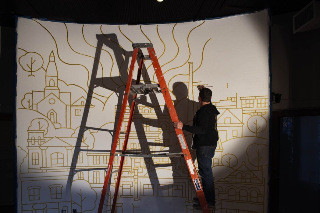 James Billiter painting a mural for the OMS studio far away with shadows up on a ladder