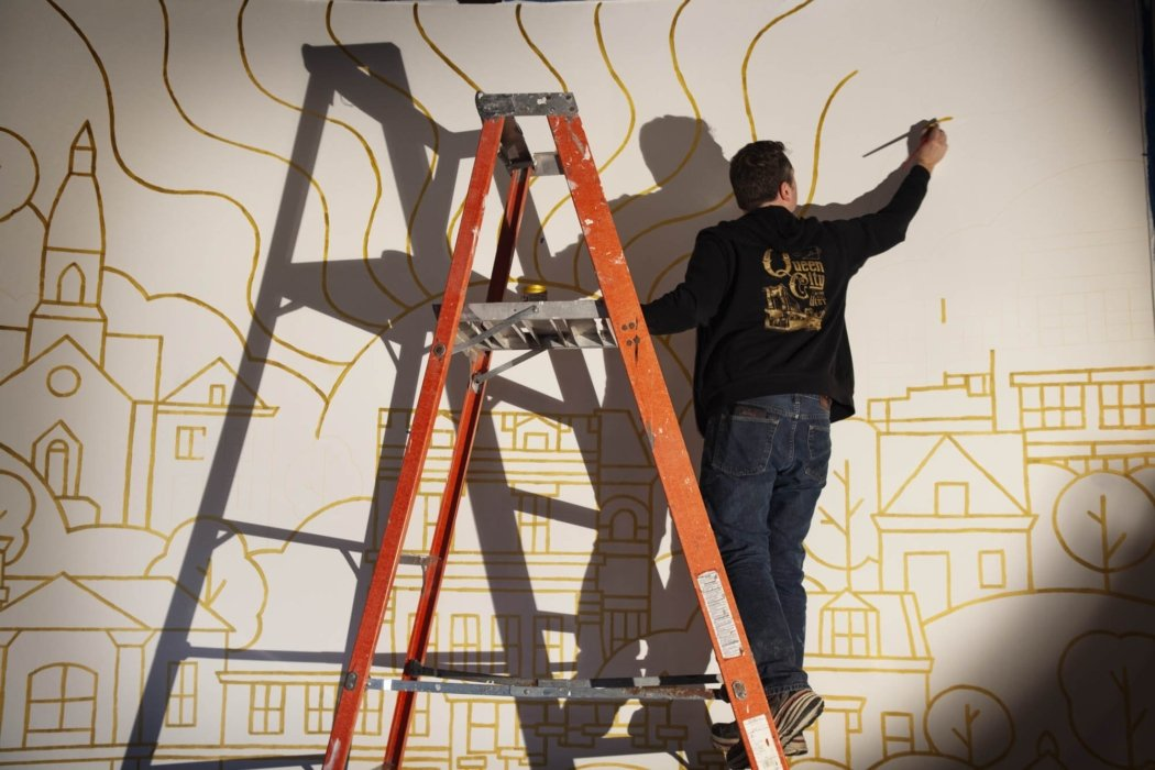 James Billiter painting a mural for the OMS studio far away with shadows up on a ladder stretching arm