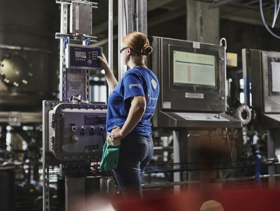 A female worker selecting settings on an industrial machine in the workplace