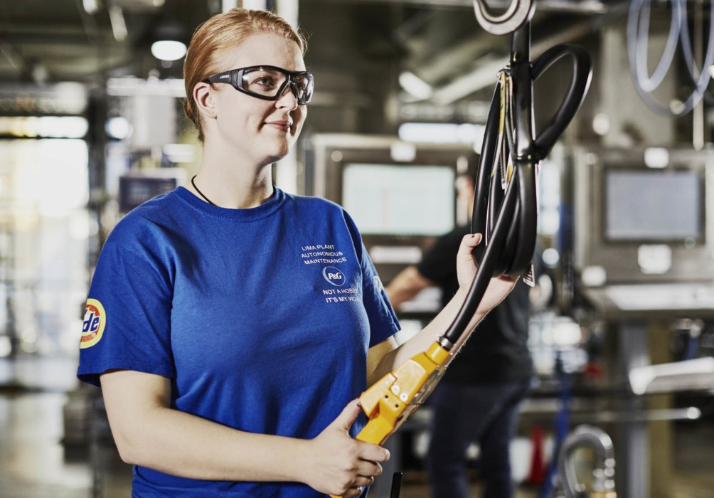 A woman inspecting and controlling industrial equipment in the workplace