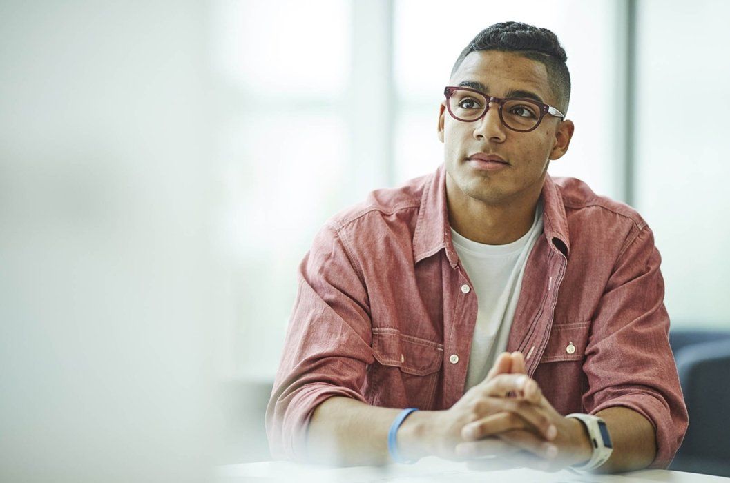 A young man listening in a meeting in an office workplace meeting