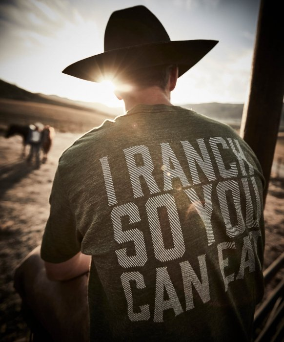 A man sitting on a fence on a ranch - work apparel photography