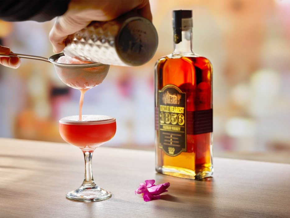 Pink and flowery whiskey cocktail being poured - drink photography