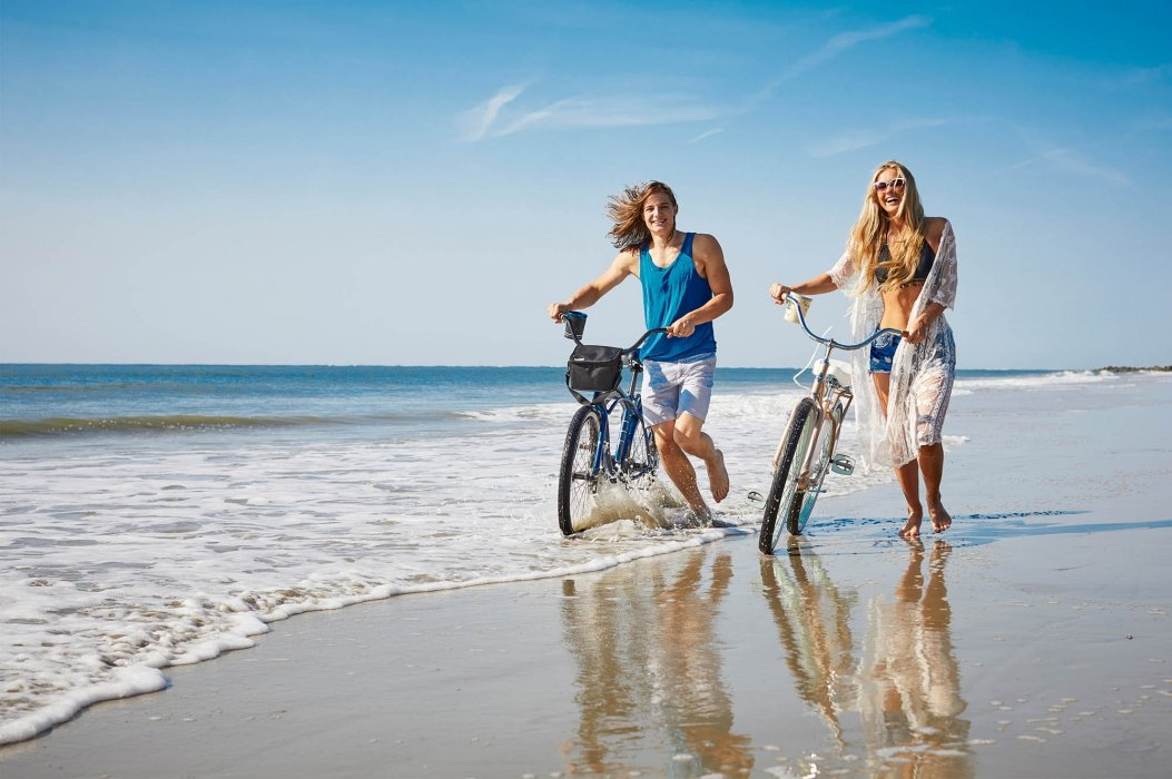 A young couple walking with bikes on a beach looking happy - lifestyle photography