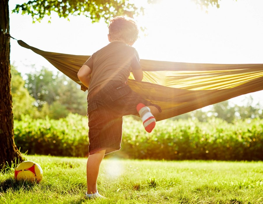 A young boy climbing into a hammock - lifestyle photography
