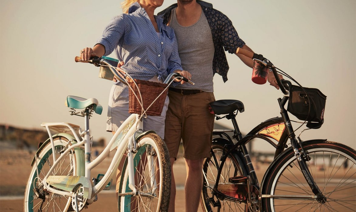 A couple on a beach walking their bikes - lifestyle photography