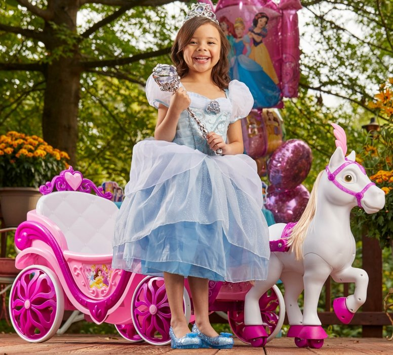 Portrait of a young girl in princess outfit next to prince toy carriage - lifestyle photography