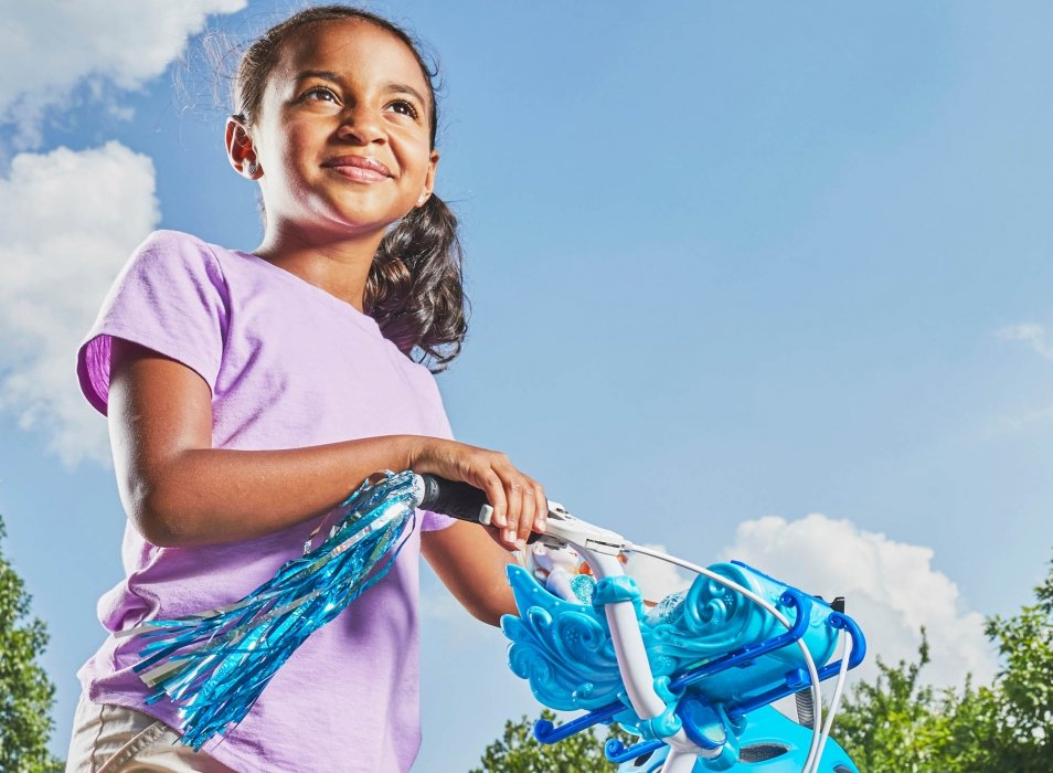 Portrait of a young girl walking her bike