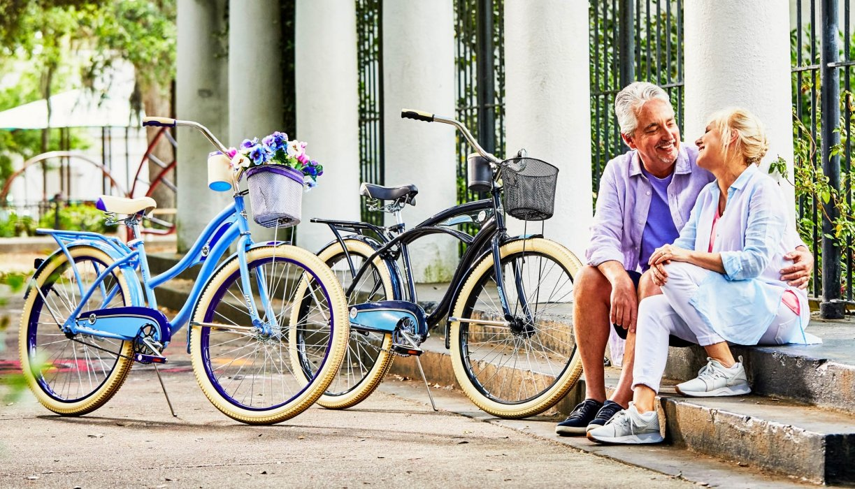 A middle aged couple sitting down in a park next to their bike - lifestyle photography