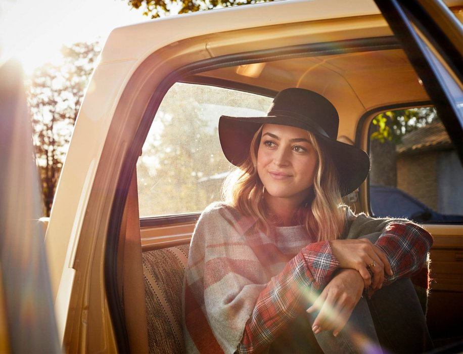 A woman sitting an a retro truck with fashionable clothing - lifestyle photography