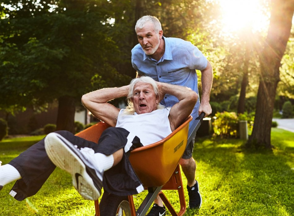 A hilarious moment when two older men are running with a wheel barrow - lifestyle photography