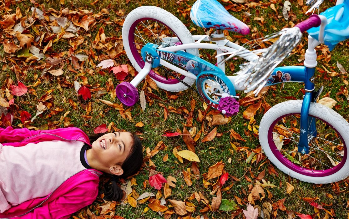 Girl laying next to bike in autumn with leaves - lifestyle photography