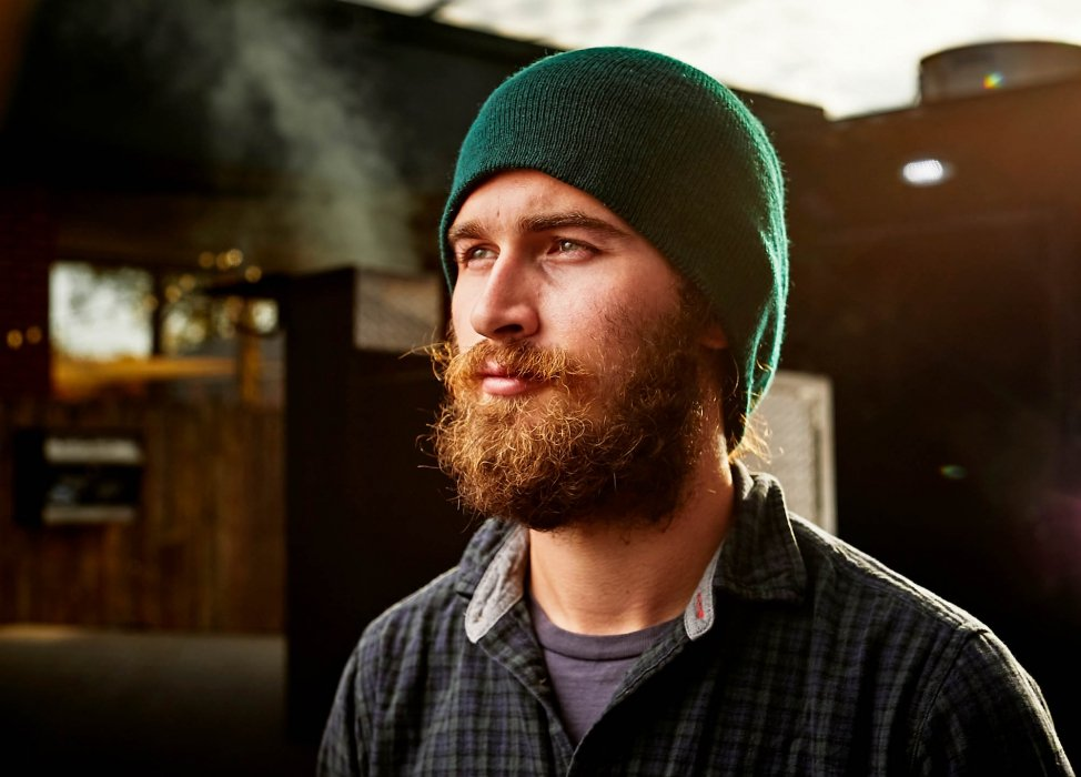 Portrait of a man with a beard near a smoke house wearing green hat