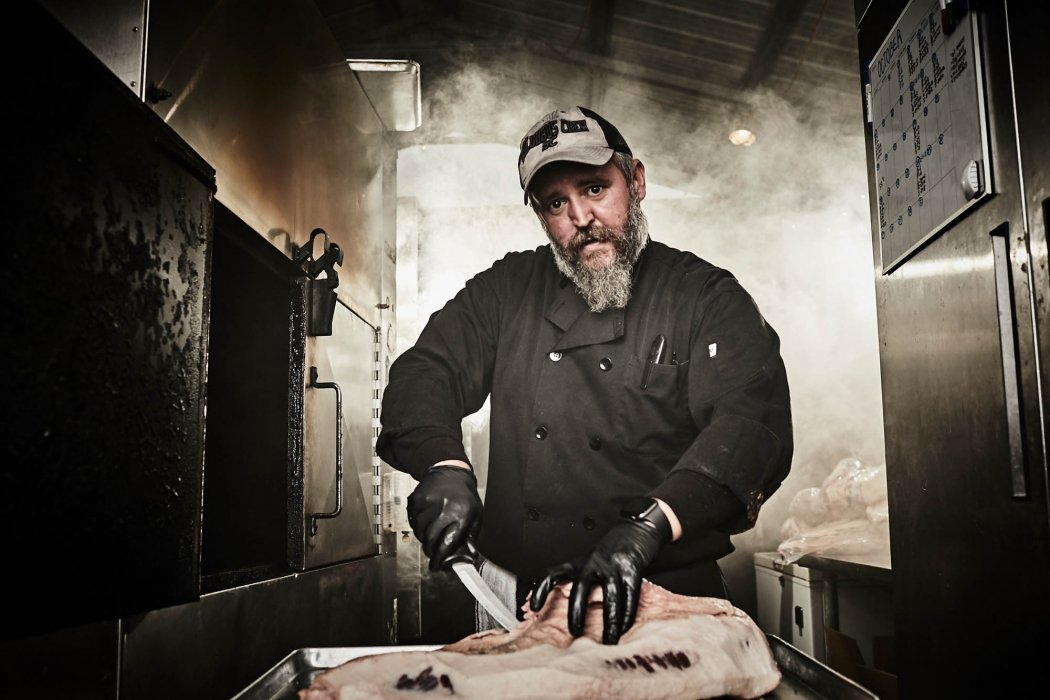 Portrait of a man working in a smoke house on meat