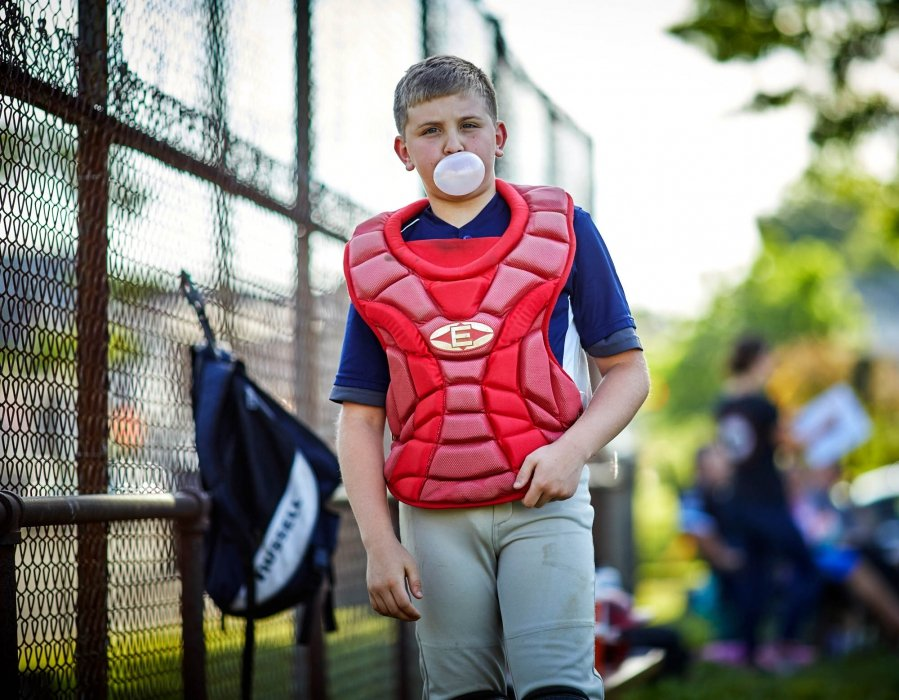 A young baseball catcher blowing a bubble at a base ball game - sport photography
