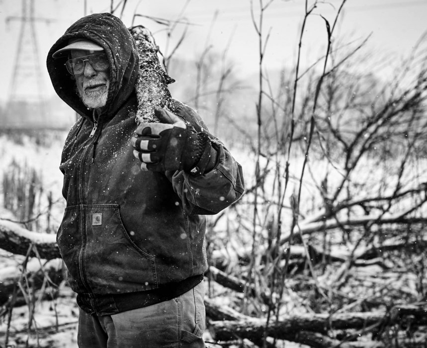 An old man working on a farm in winter with wood on shoulders - lifestyle photography