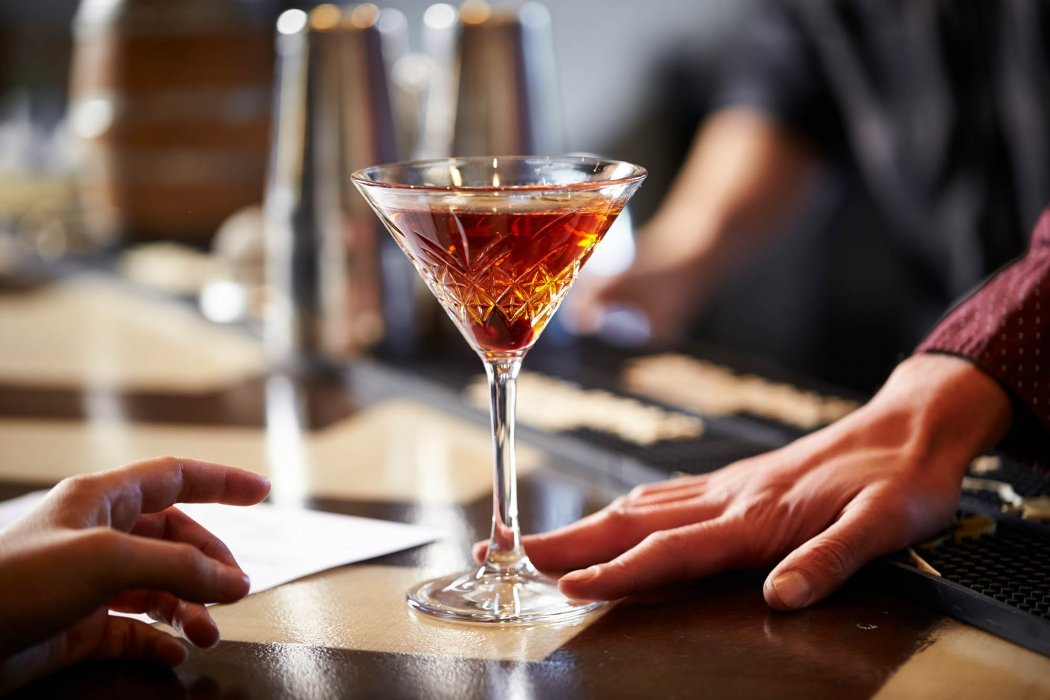 A cocktail at a bar with people - drink photography