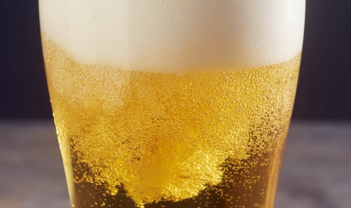 Foaming beer in the a tall pint glass with head - drink photography