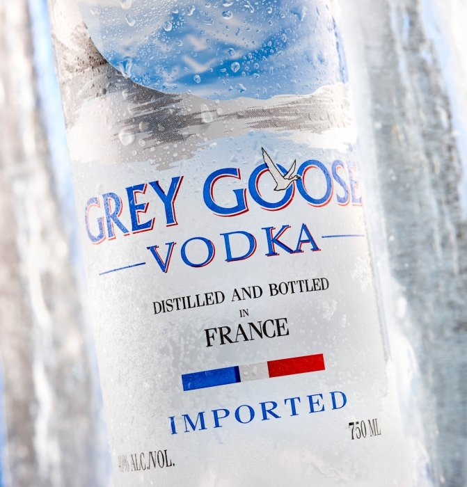 A grey goose vodka with a large ice block - Drink Photography