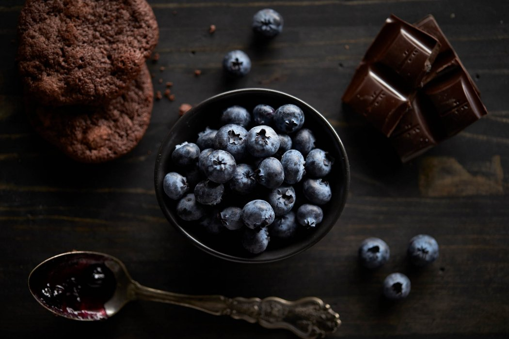 A bowl of blueberries and chocolate on dark wood - food photography