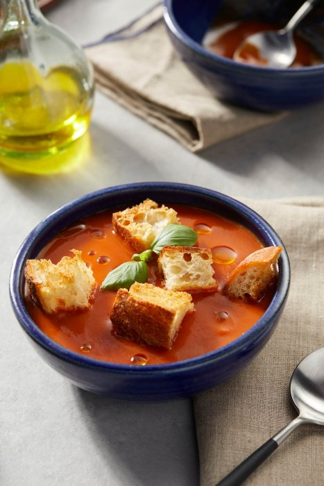 High end pottery ceramic plates and bowls with tomato soup and olive oil and croutons product photography