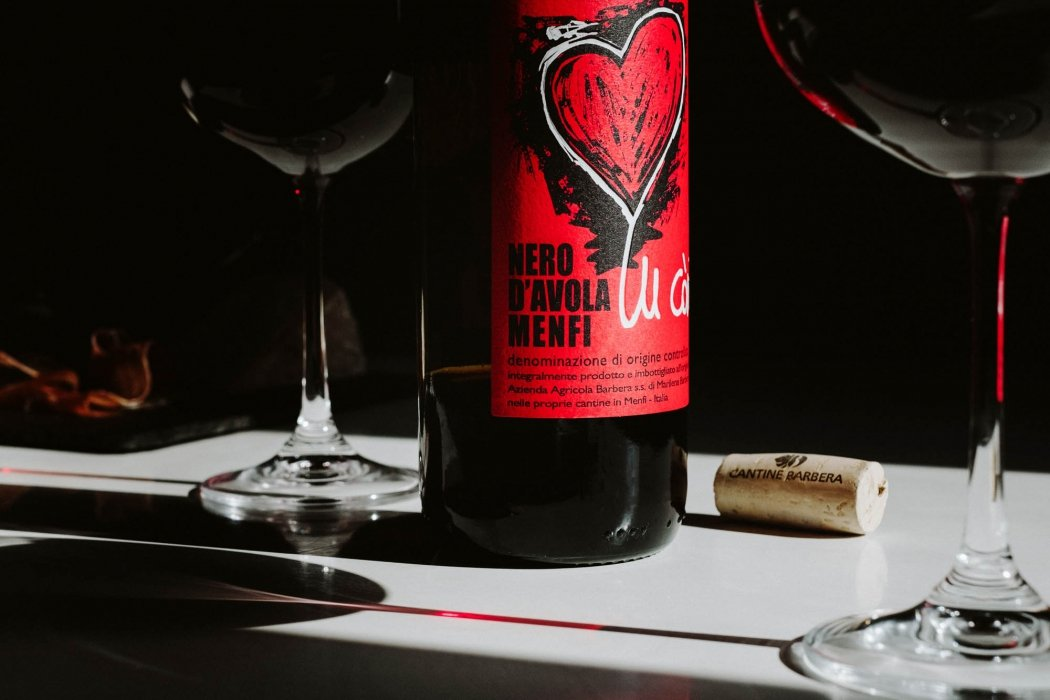 Nero d'avola menfi wine on table with dark lighting - wine photography