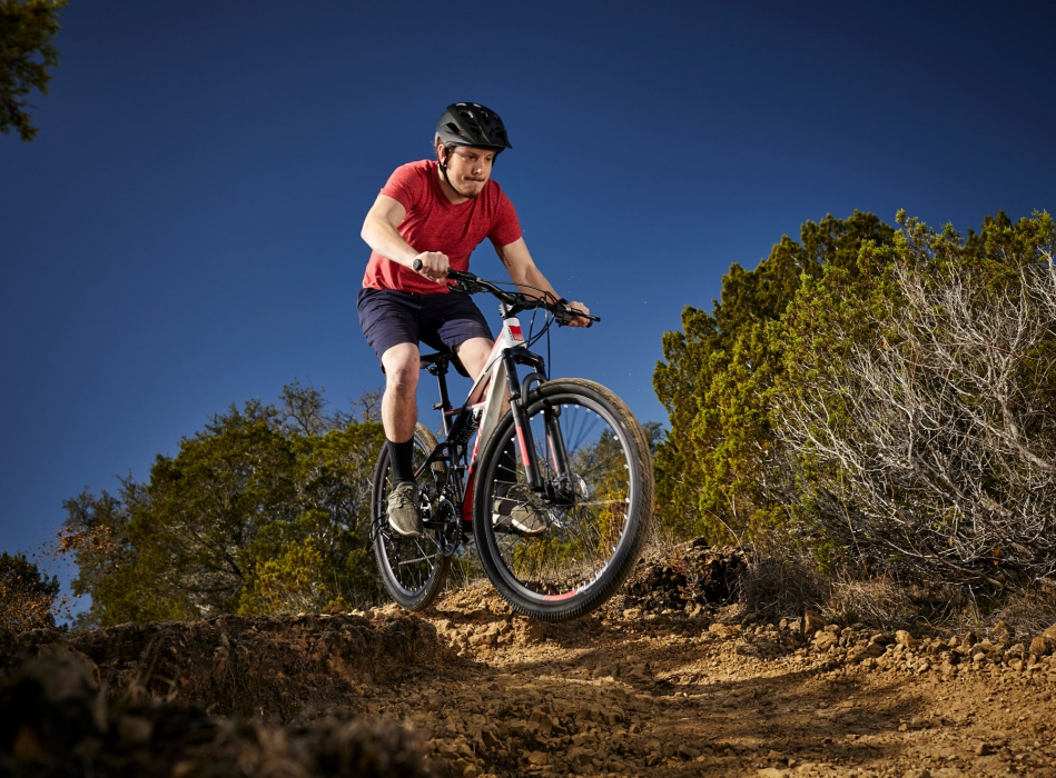 A man with huffy bike riding through rugged terrain - product lifestyle photography