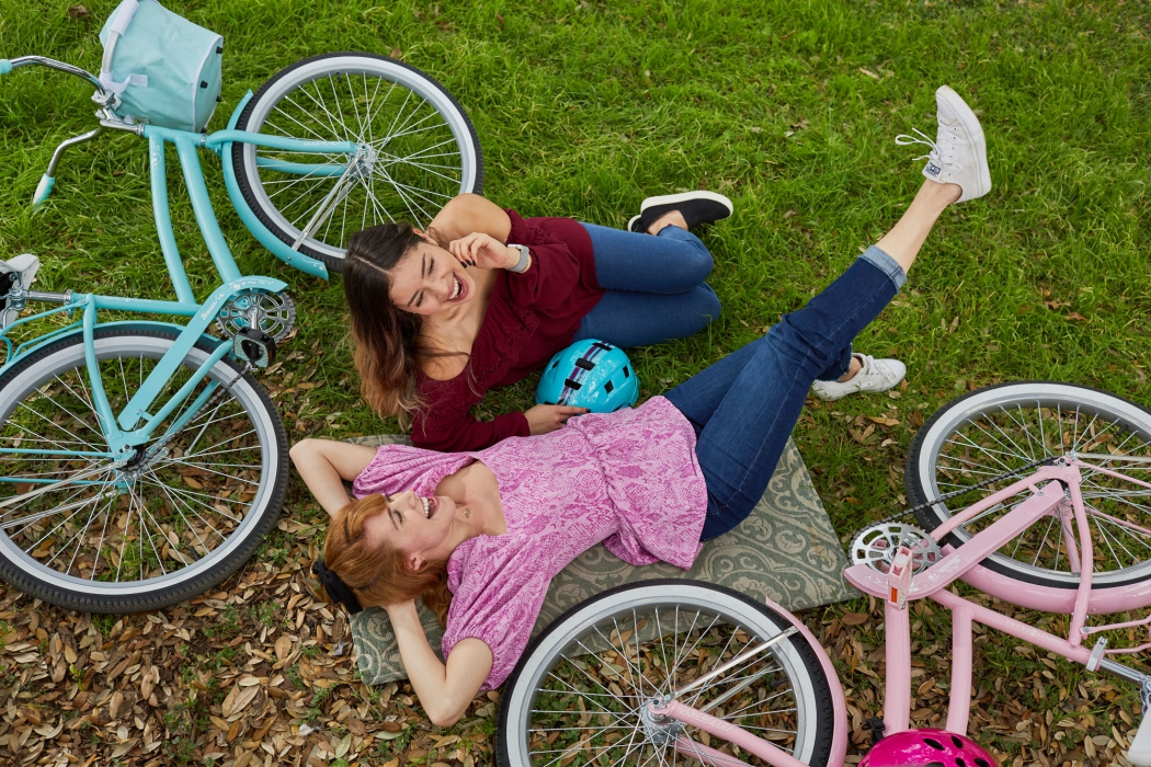 Two girl friends enjoying their colorful vintage style bikes - product lifestyle photography
