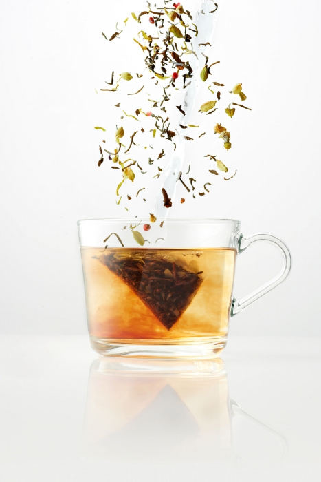 Hot tea falling into a glass tea cup - drink photography