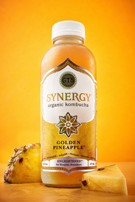 Synergy organic kombucha with golden background and golden pineapples - drink photography -