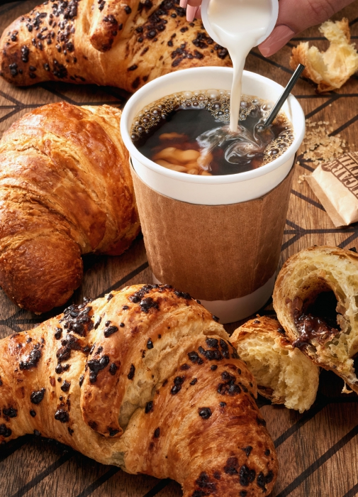 Fresh baked crossants and neatly poured coffee and cream - drink photography